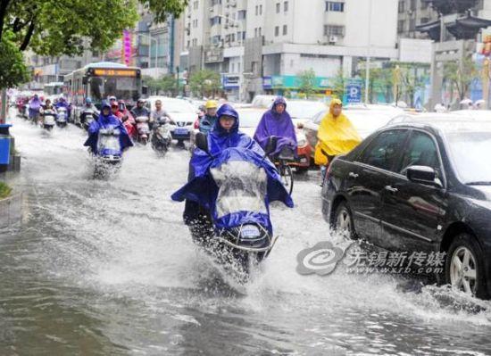 昨天下午锡城出现雷雨大风和短时强降水等强对流天气。图为市民路过已积水的县前东街。(还月亮摄)