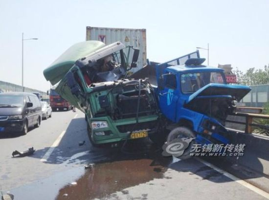 """一辆挂上海牌照的集装箱半挂车和一辆蓝色的农用车紧紧""""缠""""在一起"""